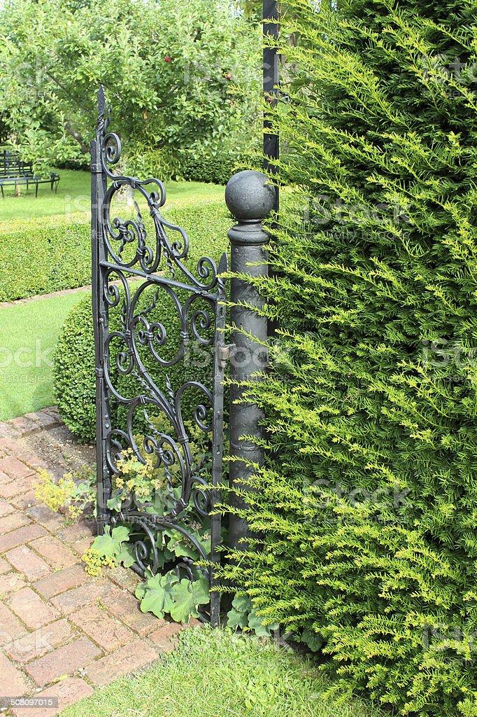 Formal garden, brick paved path, ornate iron gate, yew hedge stock photo