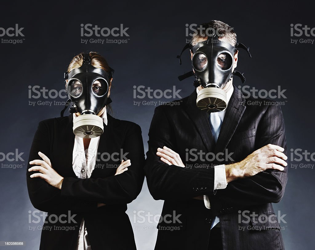 Formally dressed couple in gas masks fold arms and stare stock photo