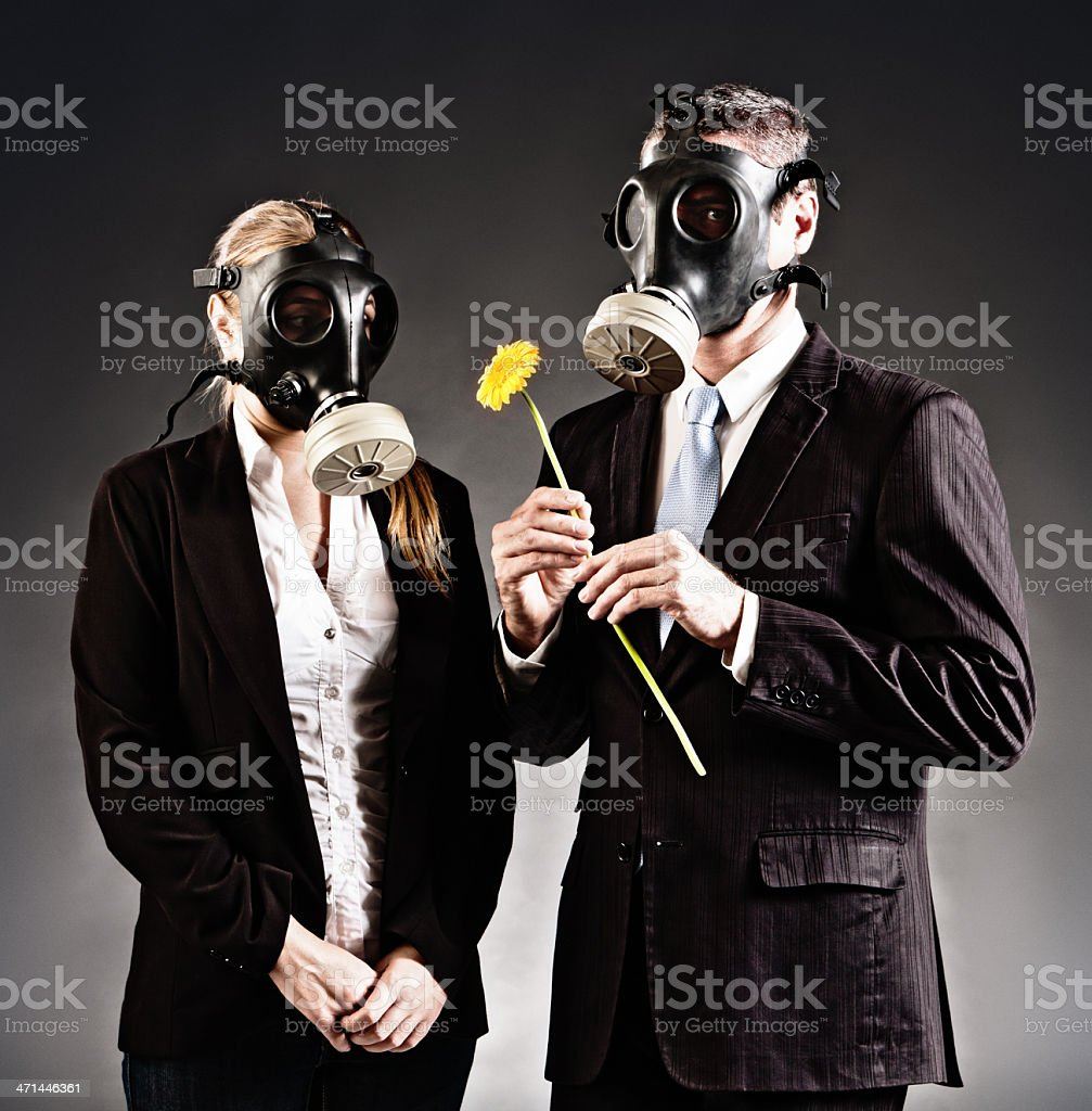 Formally dressed couple in gas masks with yellow flower stock photo