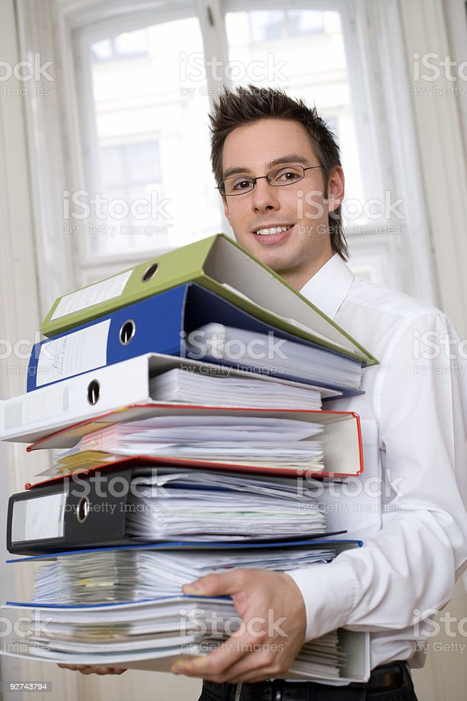 Formally dressed young man carrying a bunch of files stock photo