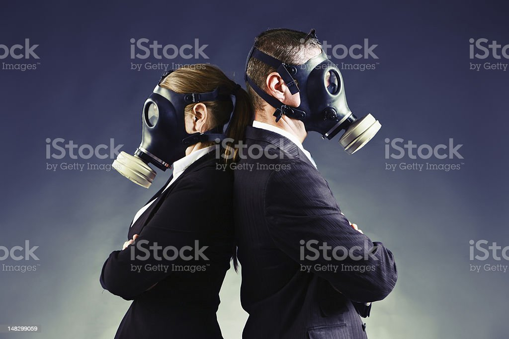 Formally-dressed couple in gas masks stand backs to each other stock photo