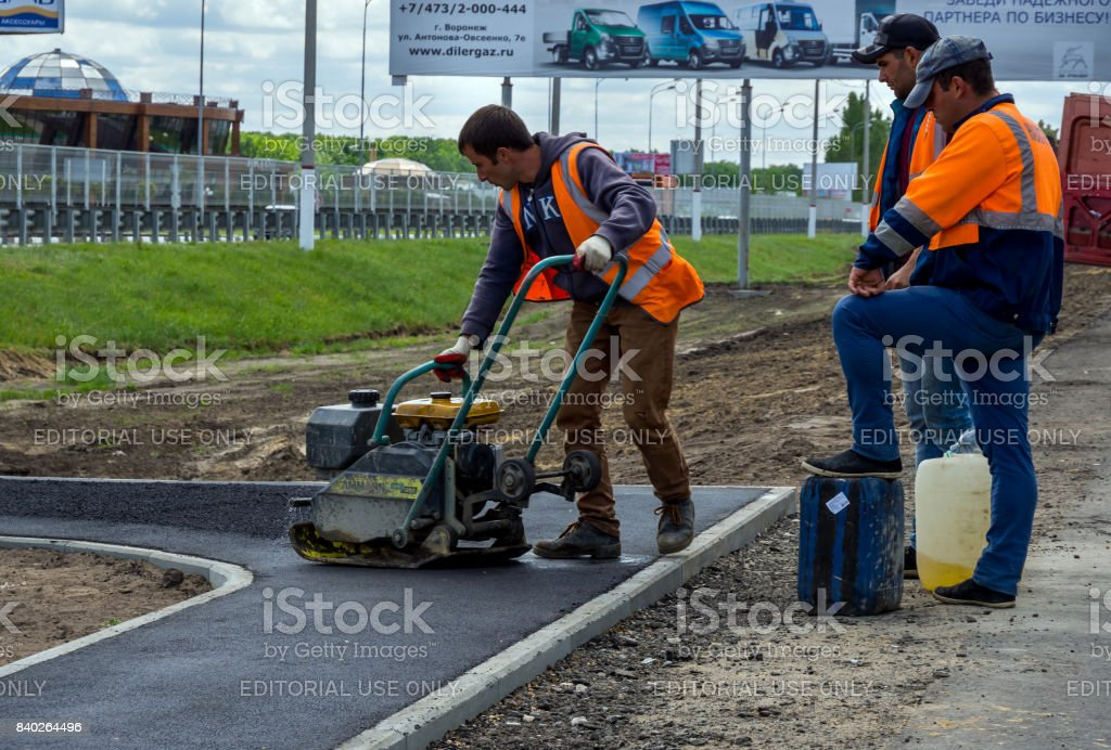 Formation of an asphalt layer on the sidewalk using a vibrating machine in Moskovsky prospect stock photo