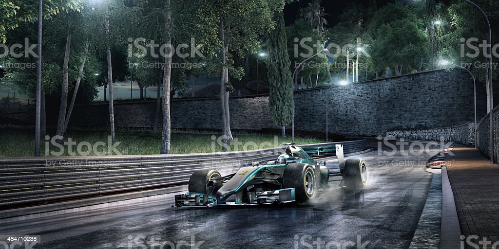 A green and silver racing car travelling at speed on a generic...