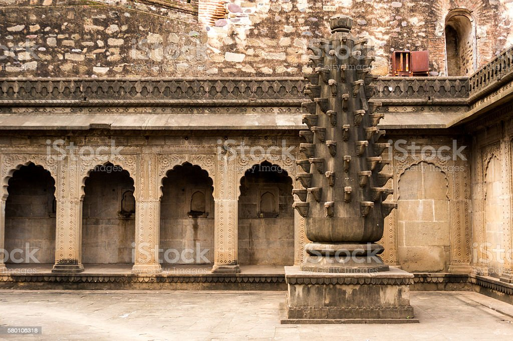 fort in maheshwar, india with arches and a carved pillar stock photo