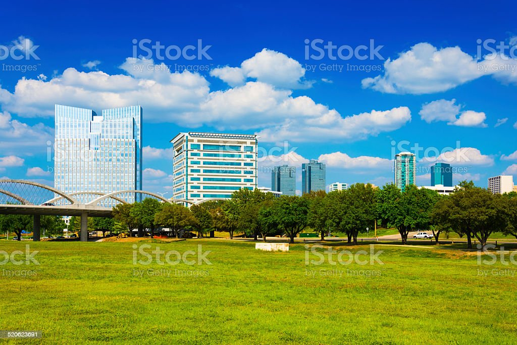 Fort worth skyline with puffy white clouds from a park stock photo