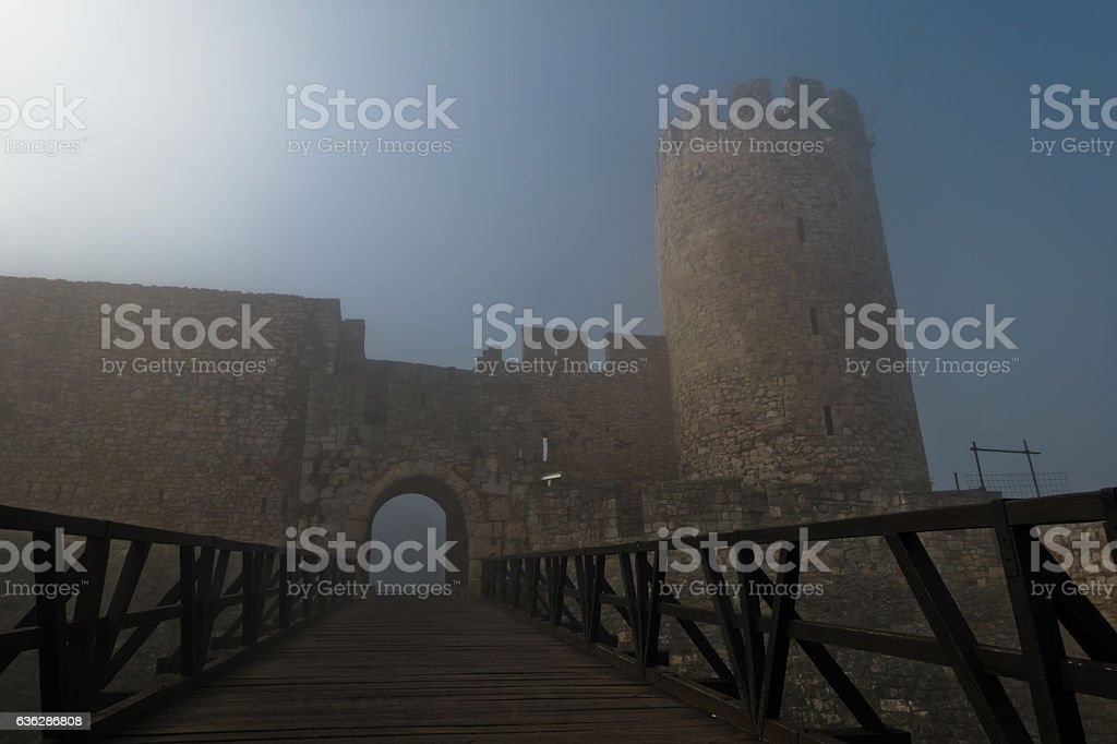 Fortress tower, gate and wooden bridge in fog at morning stock photo