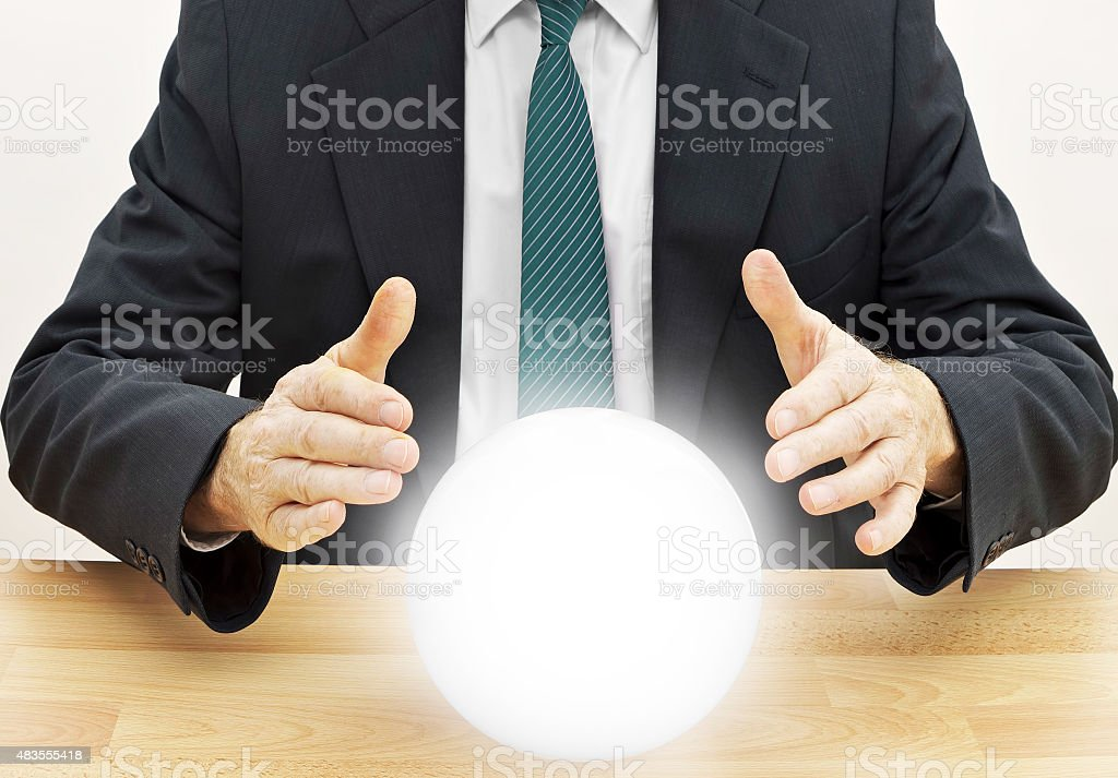 Fortune teller businessman predicting future with crystal ball stock photo