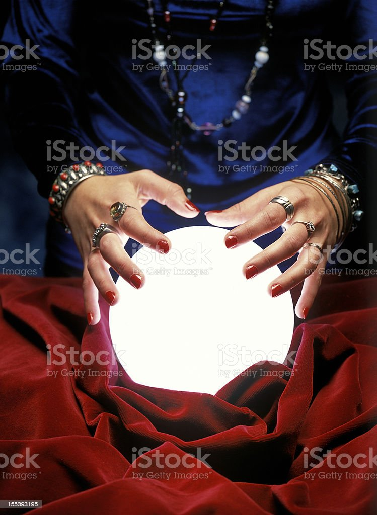 fortune teller hands on glowing crystal ball stock photo