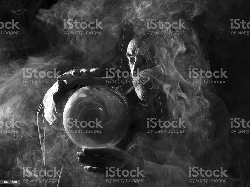 Fortune teller in fantastical costume holding crystal ball stock photo