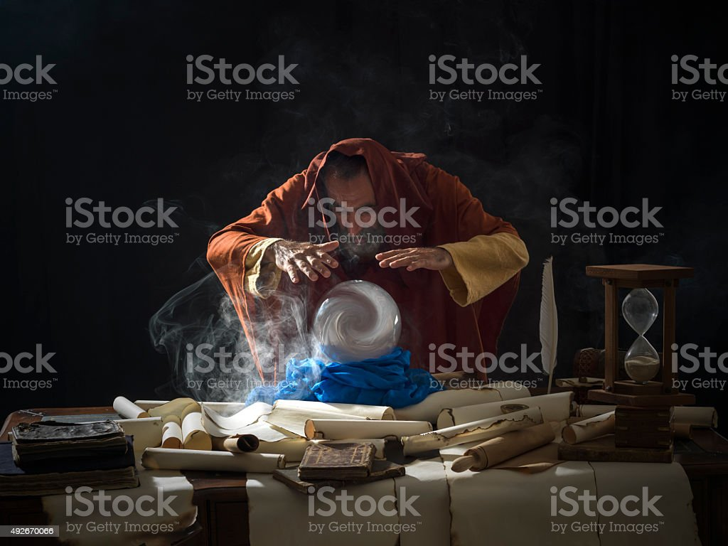 Fortune teller in fantastical costume using crystal ball stock photo