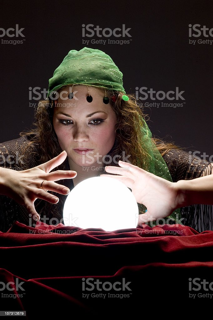 fortune teller looking at glowing crystal ball royalty-free stock photo