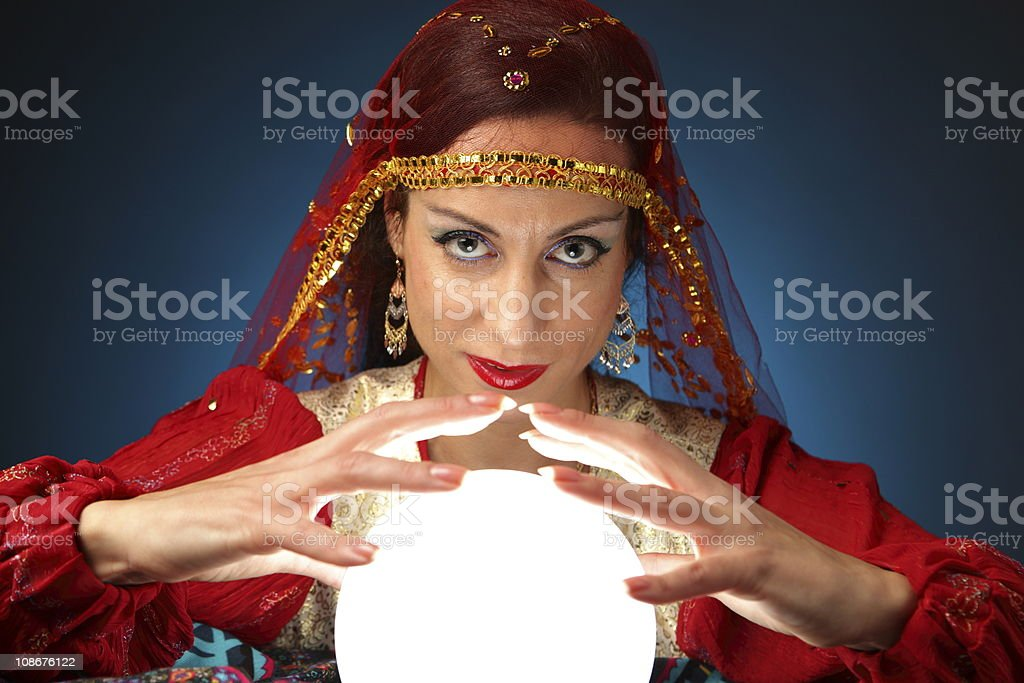 A fortune teller with a glowing globe stock photo