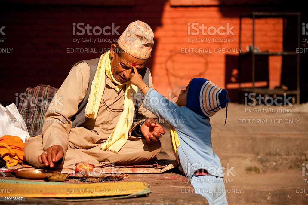 Fortune tellers gets a bindi from a little boy. stock photo