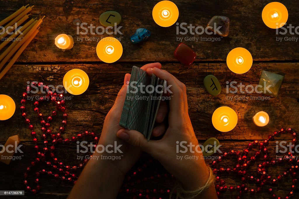 fortuneteller reads fortunes by tarot cards and candles stock photo