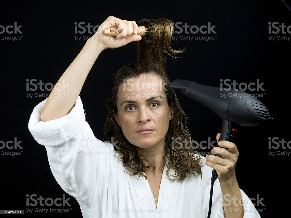 Forty something Caucasian female drying her hair royalty-free stock photo