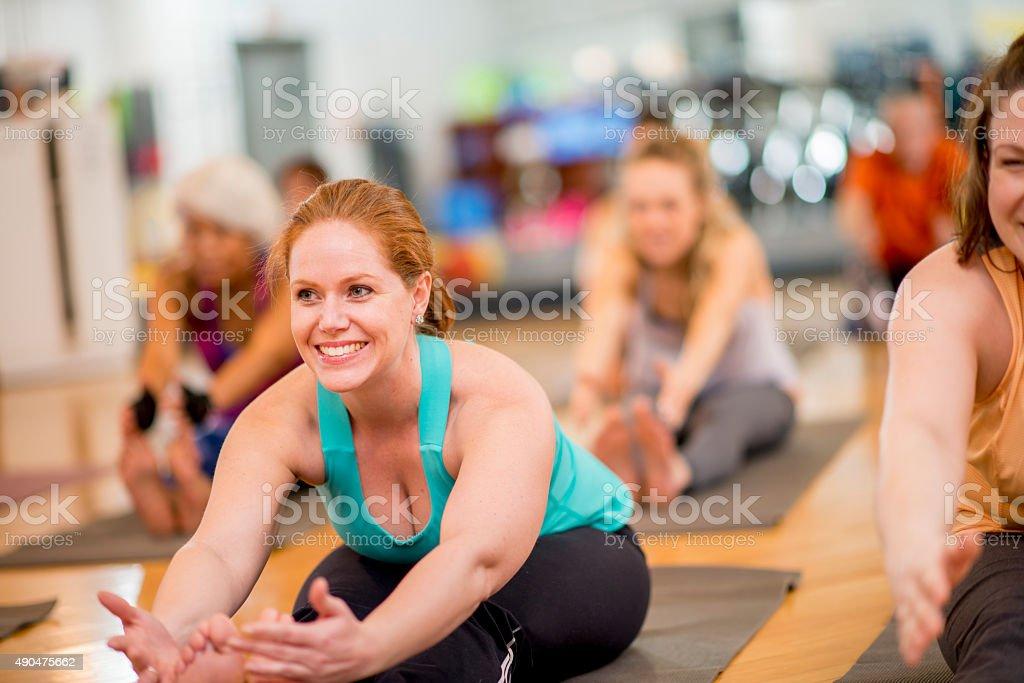Forward Fold in Yoga Fitness Class stock photo