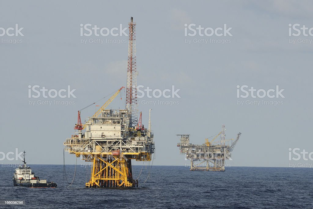 Fossil fuel production platforms and supply vessel stock photo