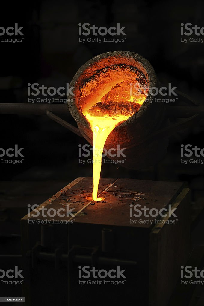 Foundry - molten metal poured from ladle into mould stock photo