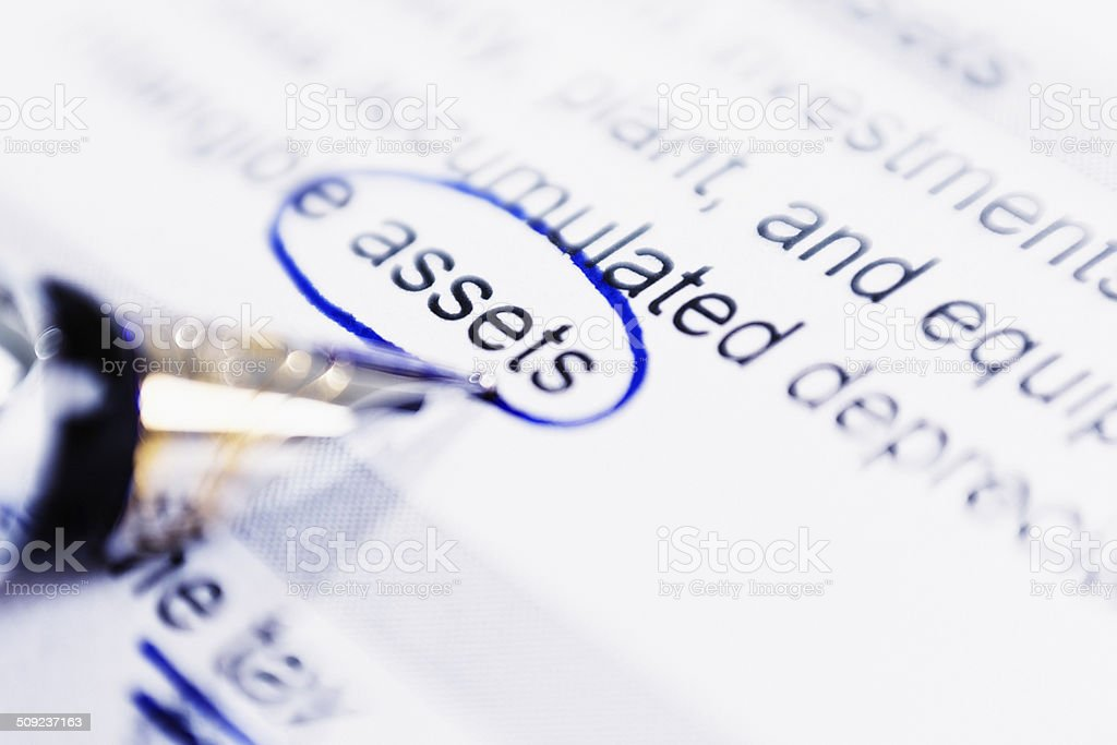 Fountain pen circles 'assets' in financial or business document royalty-free stock photo