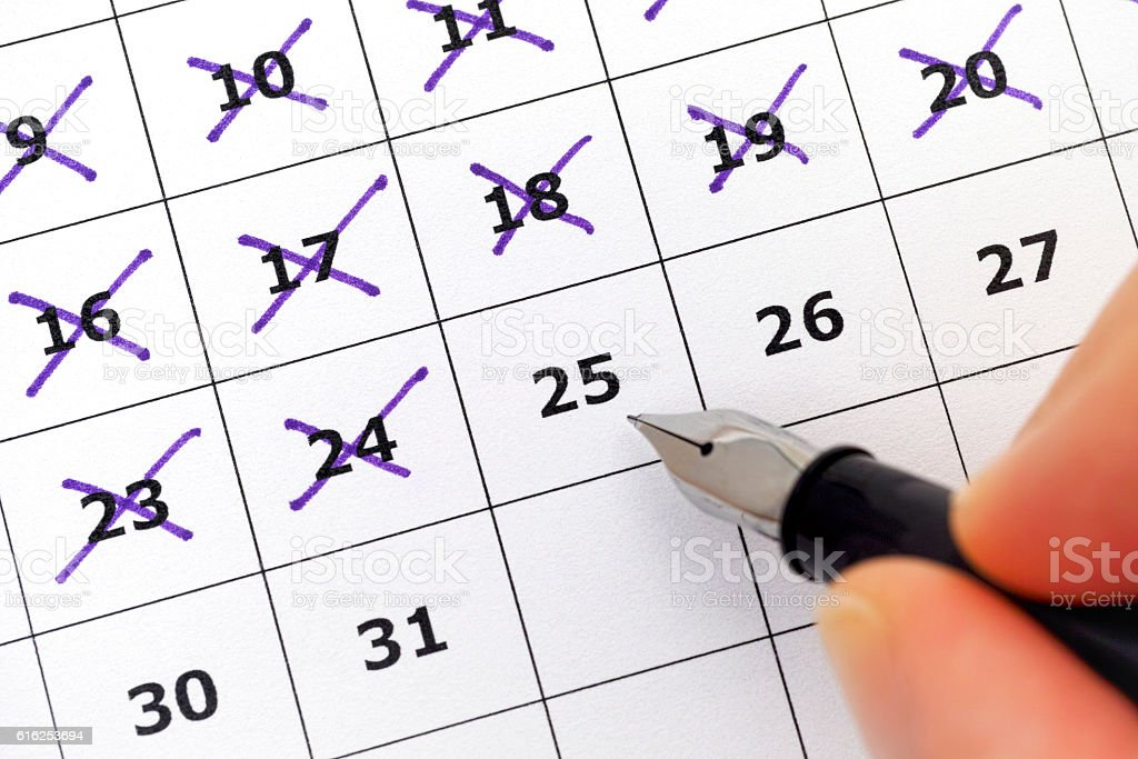 Fountain pen in person hand marking days on calendar stock photo