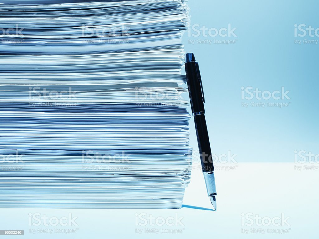 Fountain pen leaning against stack of paper stock photo