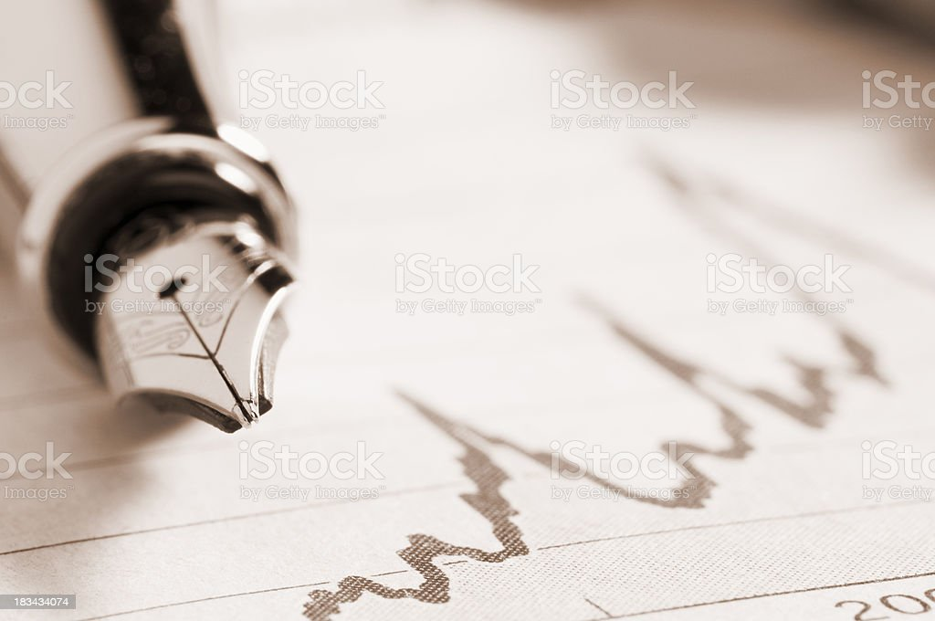 Fountain pen lying on a graph in newspaper royalty-free stock photo