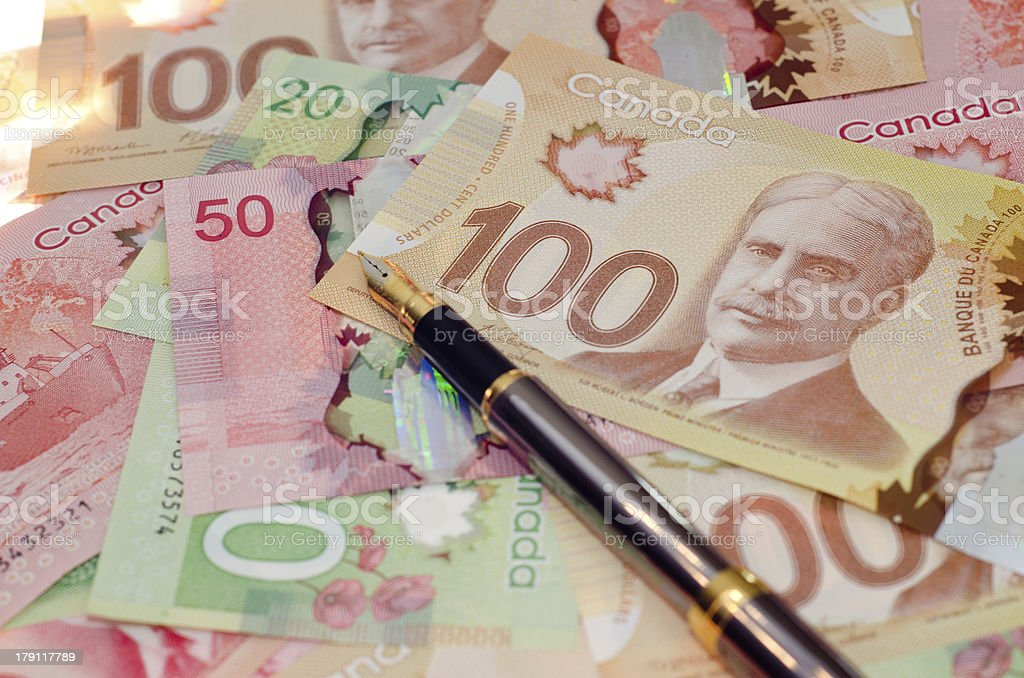 Fountain pen on a pile of money royalty-free stock photo