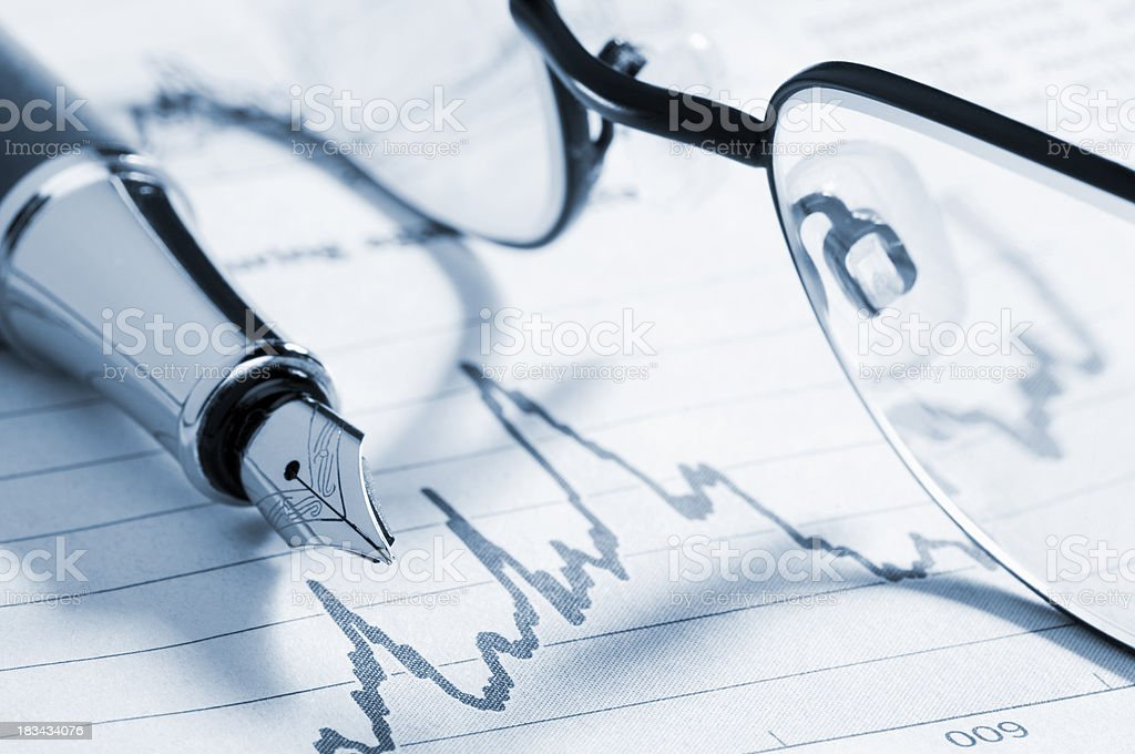 Fountain pen on graph in newspaper with reading glasses royalty-free stock photo