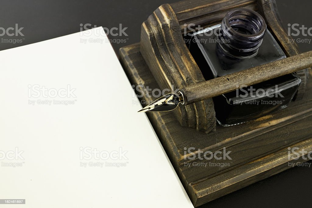 Fountain pen on ink pot and white book stock photo
