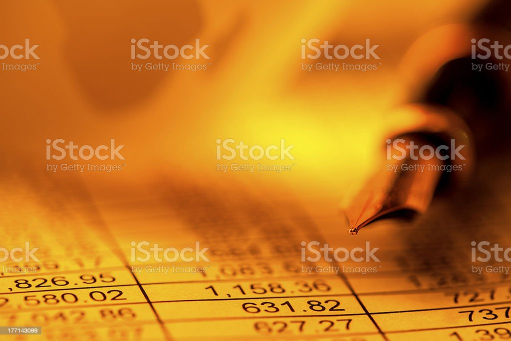 A fountain pen on top of the global finances royalty-free stock photo