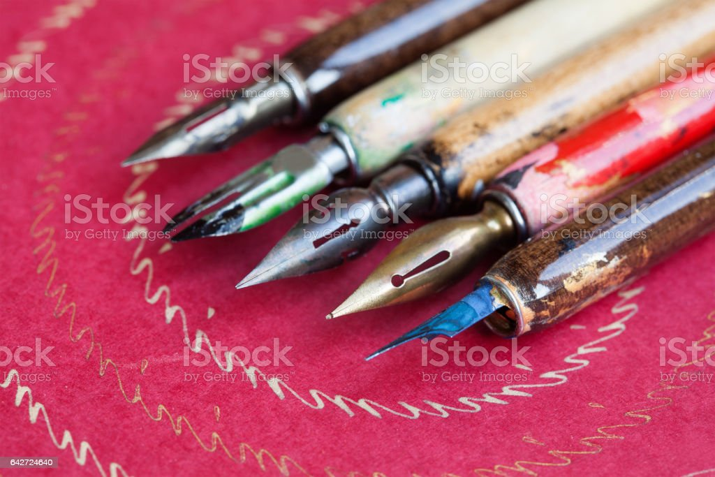 Fountain pen set. Calligraphy handwriting accessories, vintage colorful artist pens, textured pink paper background. macro view, shallow dept of field, soft focus stock photo
