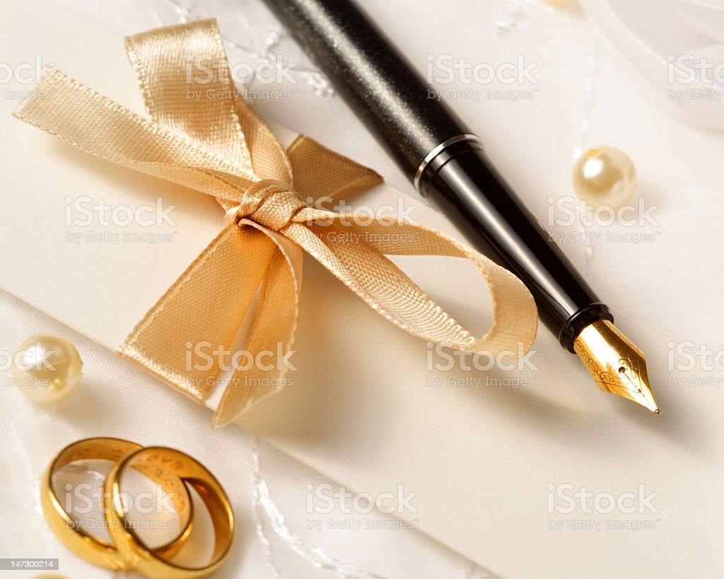 Fountain pen wedding invitation and gold wedding rings stock photo