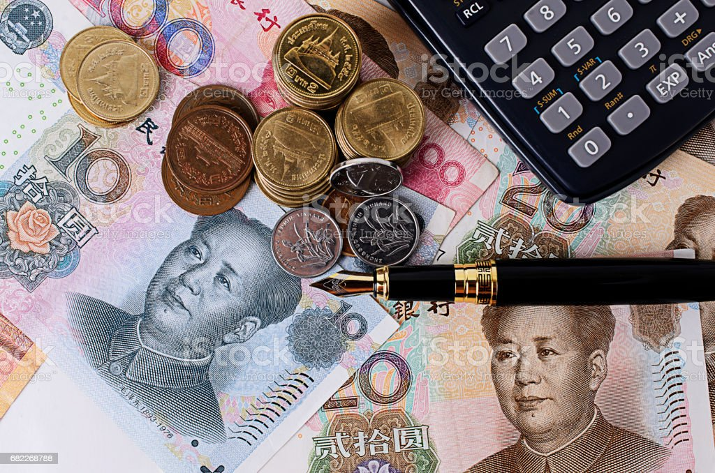 Fountain pen with coins and china banknote and calculator stock photo