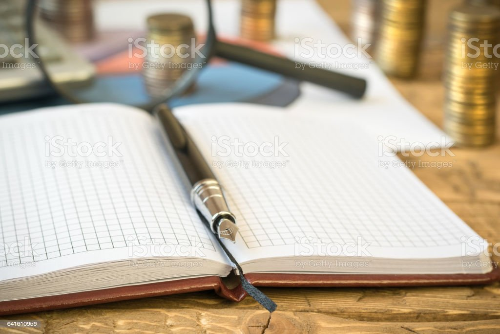Fountain pen,calculator, coins and notebook on a wooden table. stock photo