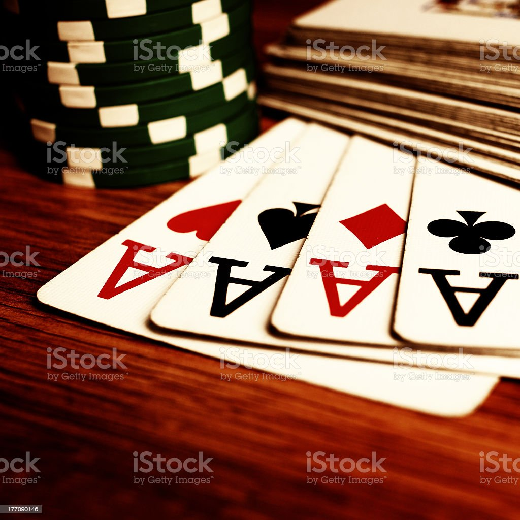 Four aces and black poker chips on wooden table stock photo