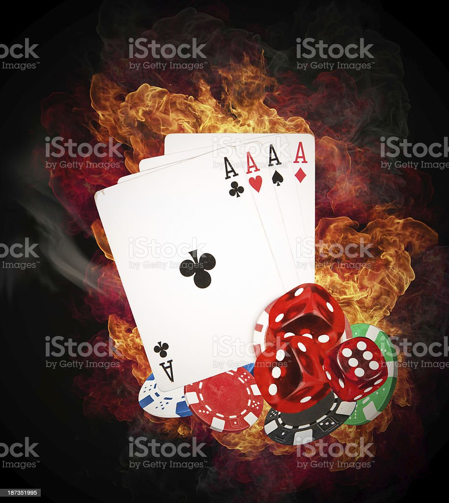 Four aces, poker chips and die on fire stock photo