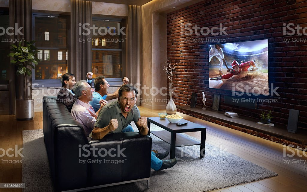 Four adult men cheering and watching Baseball game on TV stock photo