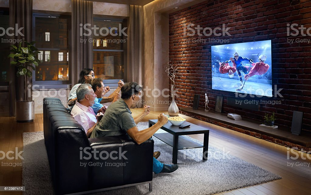 Four adult men watching Ice hockey game on TV stock photo