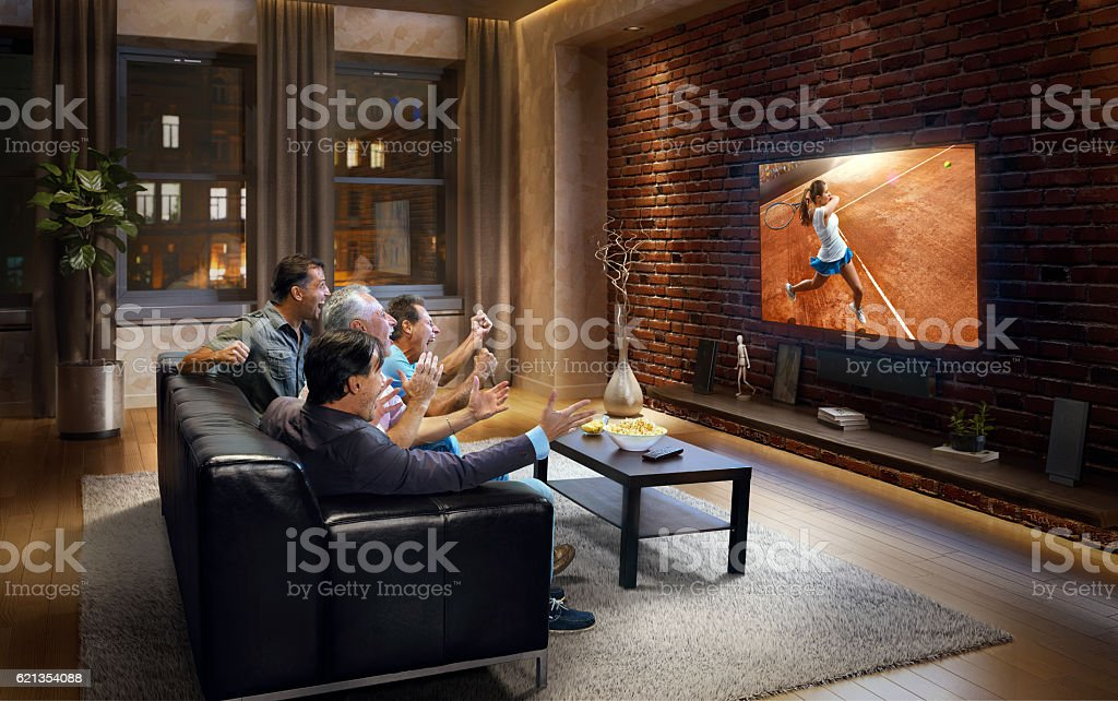 Four adult men watching Tennis game on TV stock photo