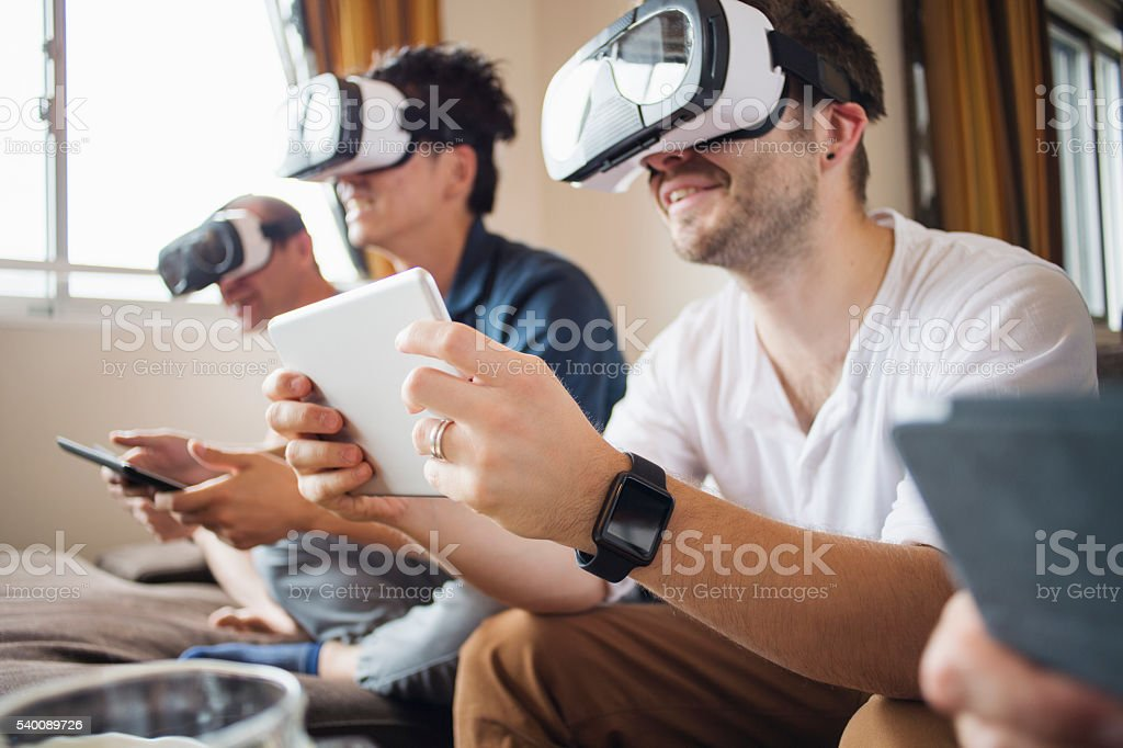 Four adults to play with a virtual reality headset stock photo