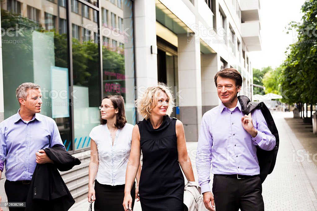 Four Adults Walking in the City stock photo