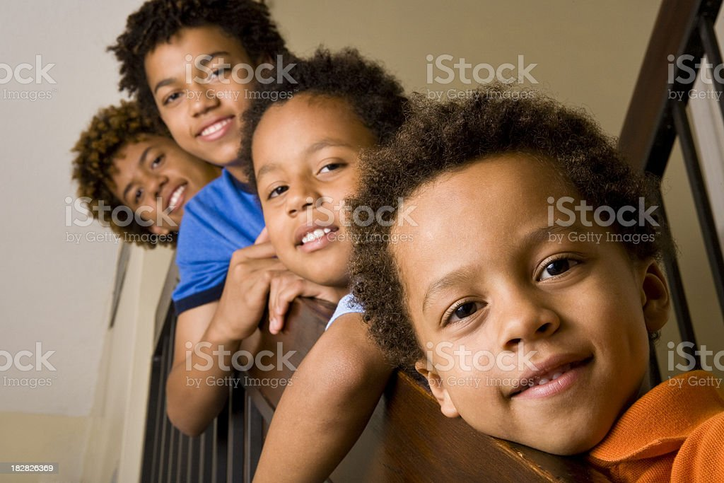 Four African ethnicity boys staning on stairs in a row stock photo