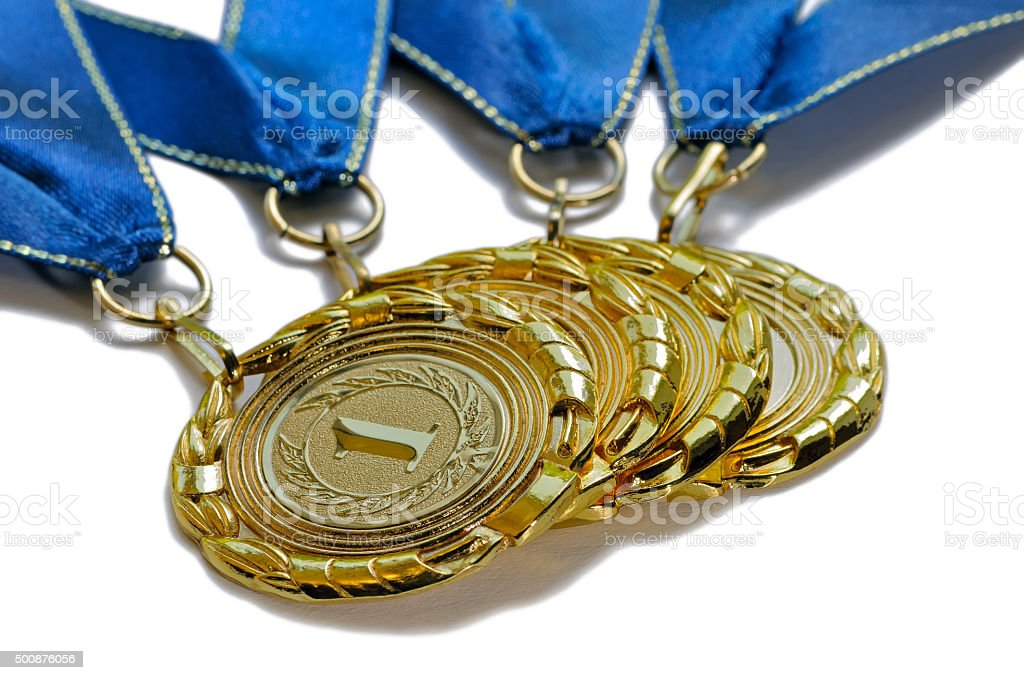 Four award medals of gold color with blue ribbons stock photo