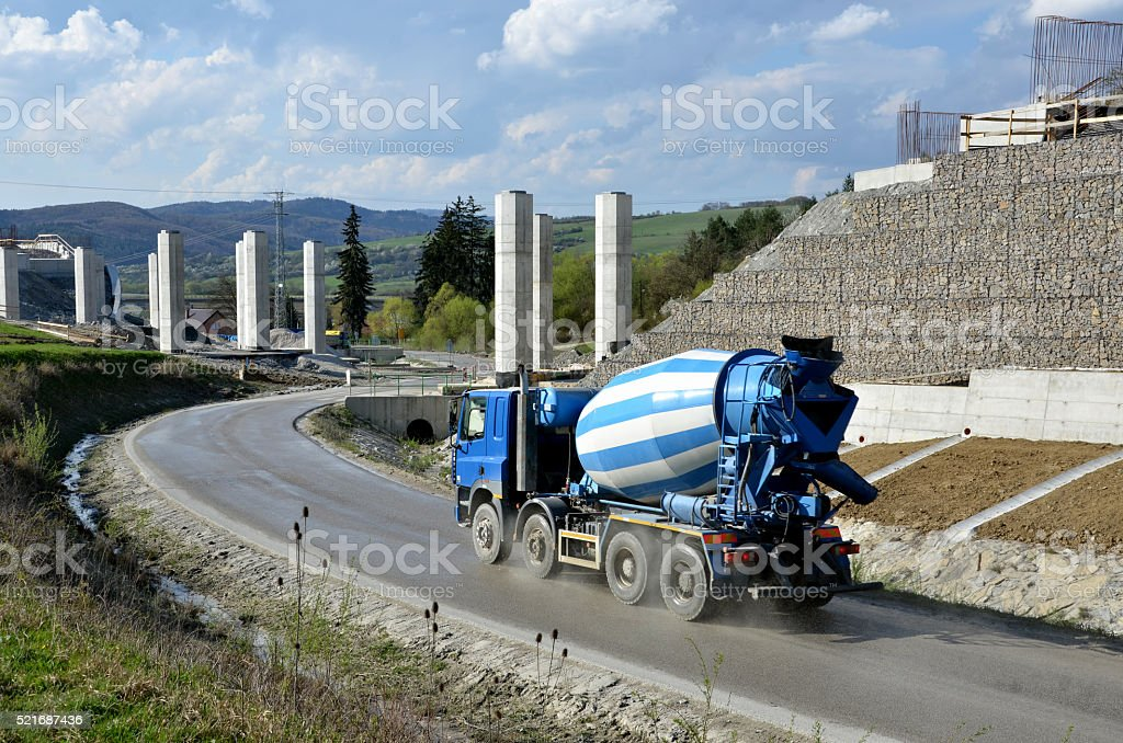 Four axles truck mixer near by highway under construction stock photo