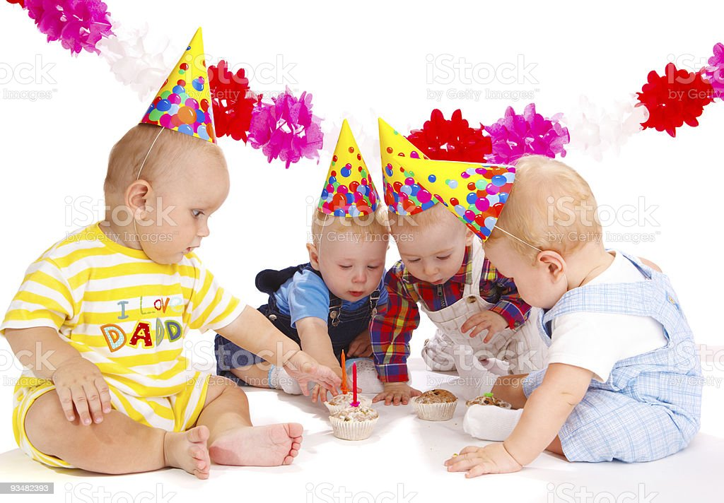 Four babies celebrating a birthday wearing party hats stock photo