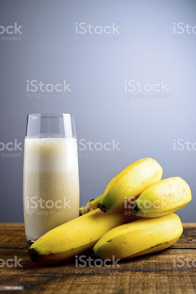 Four bananas by the side of a banana milkshake royalty-free stock photo