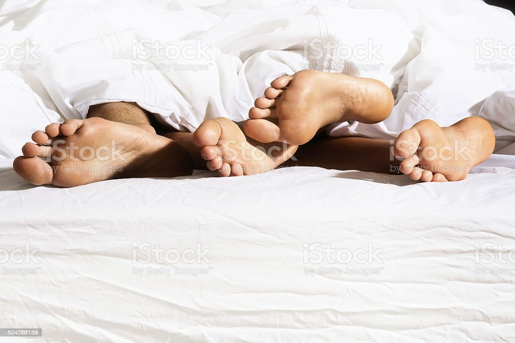 Four bare feet in bed. Female tickles male flirtatiously royalty-free stock photo
