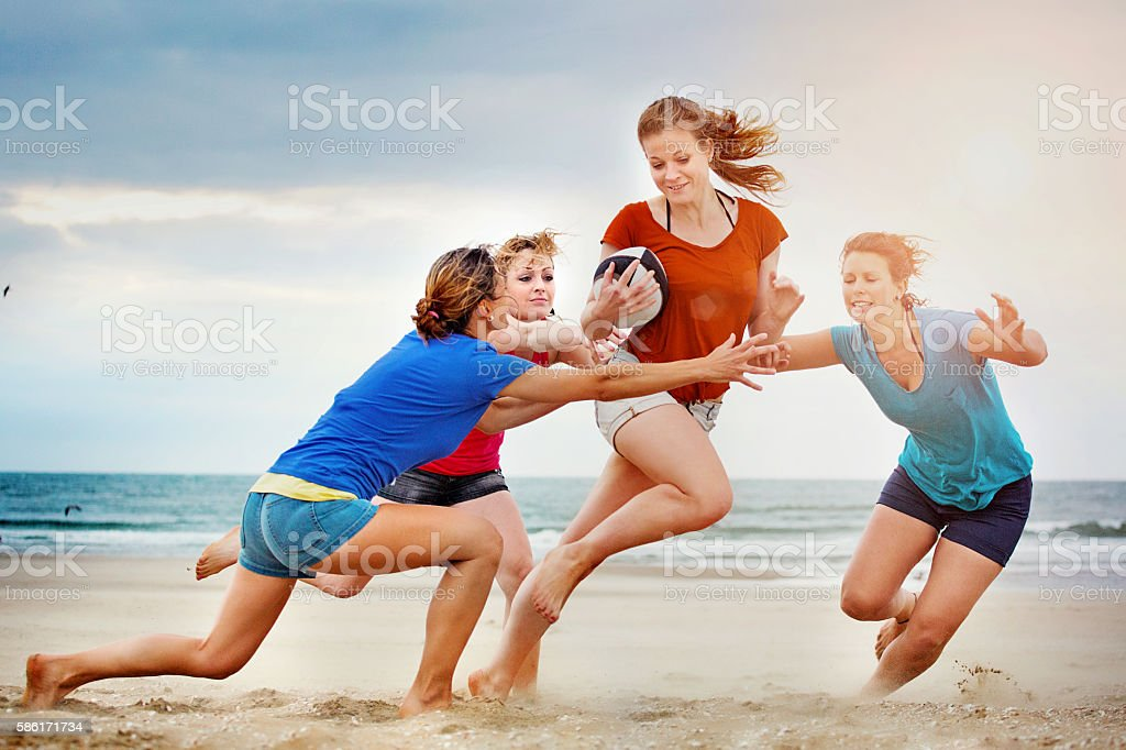 Four beautiful female friends playing beach rugby in Summer stock photo