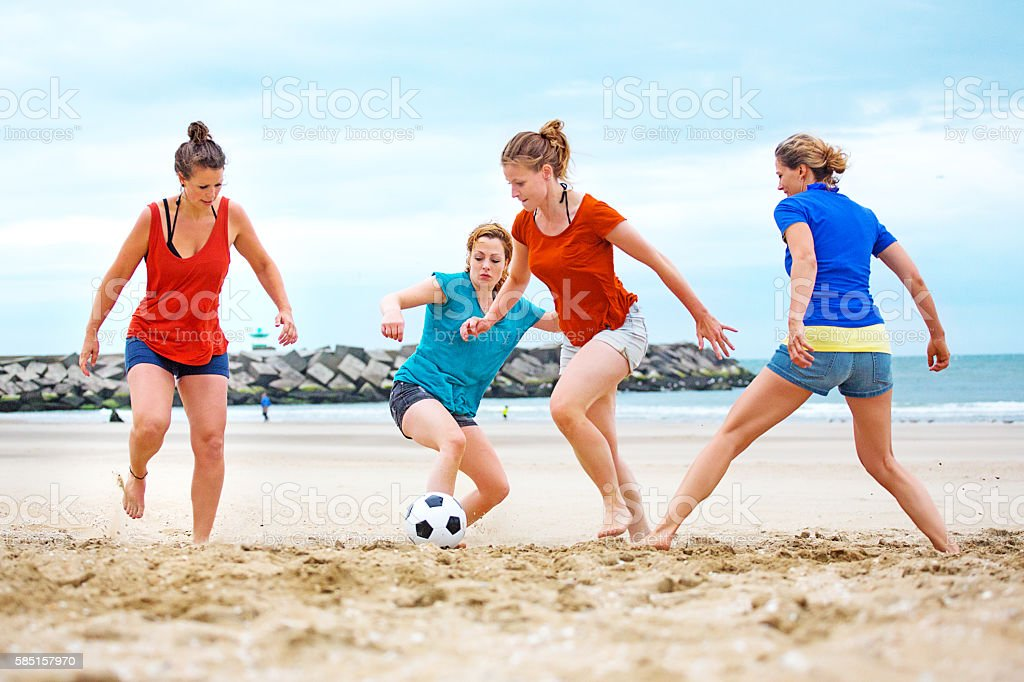 Four beautiful female friends playing beach soccer in Summer stock photo