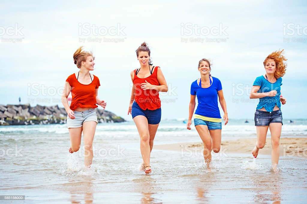 Four beautiful female friends running on sandy seashore in summer stock photo